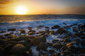 Sunset with waves on rocks towards beach at sundown Stock Image