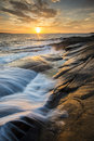 Sunset on the west coast of sweden waves sweep in over rocks in beautiful evening light Royalty Free Stock Photo