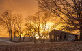 Sunset woodshed on a farm with the sun setting in the background Royalty Free Stock Photography
