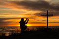 Sunset worship man beautiful as bows down to god before a cross Stock Images