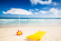 Sunshade with air mattress beach scene a white frisbee and yellow behind a turquoise sea and blue sky Stock Images