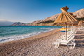 Sunshade and deck chair on beach at Baska in Krk - Croatia Stock Image