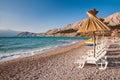 Sunshade and deck chair on beach at Baska in Krk - Croatia Stock Image