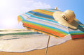 Sunshade and straw hat detail of colorful in the beach on a sunny summer day Stock Photos