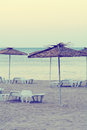Sunshades on empty beach during sunrise toned image Royalty Free Stock Photography