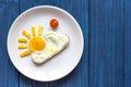 Sunshine fried eggs breakfast for kid on blue background Royalty Free Stock Photo
