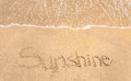 Sunshine handwritten in sand on a beach Stock Images