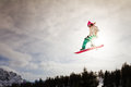Sunshine jump female snowboarder making an awesome big of a kicker Stock Photography