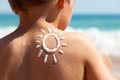 Suntan lotion at the beach child with shaped as a sun on his back concept for sun protection and skin care for children Royalty Free Stock Images