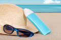Suntan lotion hat focus on sun glasses Royalty Free Stock Image