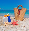 Suntan lotion and straw bag at the beach Stock Image