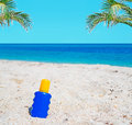 Suntan and palms lotion bottle in the sand with Stock Photos