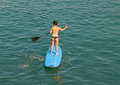 Sup paddle surf in the beach with boats background Royalty Free Stock Photography