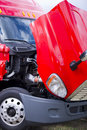 Super bright red modern semi truck engine under open hood big rig parked with to check working condition and condition of the Royalty Free Stock Photo