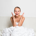 Super excited gorgeous bride sitting on a couch wedding day moments series realizing how happy she feels about the upcoming events Stock Photos