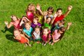 Super happy large group of kids boys and girls about years old standing on the green grass top view Royalty Free Stock Photo