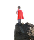 Super hero boy ready to fly on white background a young is wearing a red cape and standing a rocky cliff looking at a isolated for Stock Images