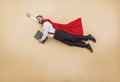 Super manager in a superman pose wearing a red cloak studio shot on a beige background Stock Image