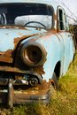 Old, abandoned rusty car wreck front and lamp. Royalty Free Stock Photo