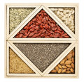 Superfood tray abstract square and triangles chia seeds dried goji berries golden flax pumpkin seeds almonds and hemp seed hearts Stock Photo