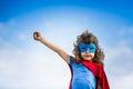 Superhero child against blue sky background Stock Photo