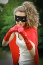 Superhero girl blond masked ready to fight wearing a red cape and red gloves Stock Photography