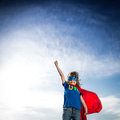 Superhero kid against dramatic blue sky background Stock Photos