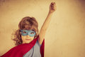 Superhero kid against grunge concrete background Royalty Free Stock Photo