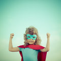 Superhero kid against summer sky background girl power and feminism concept Stock Photo