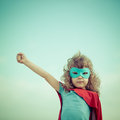Superhero kid against summer sky background girl power and feminism concept Royalty Free Stock Image