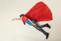 Superhero kid flying. Super hero boy in red cape and blue mask. copyspace, toned Royalty Free Stock Photo