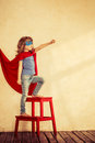 Superhero kid full length portrait of against grunge wall background Stock Images
