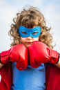 Superhero kid girl power concept wearing boxing gloves against blue sky background and feminism Royalty Free Stock Images