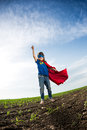 Superhero kid jumping against dramatic blue sky background Stock Photo