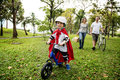 Superhero little boy riding bicycle with family in the park Royalty Free Stock Photo