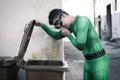 Superhero opening a trash bin Royalty Free Stock Photo