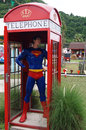 Superman in telephone box showing in amusement park Royalty Free Stock Images