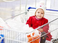 Supermarcet with baby happy lovely sitting in shopping trolley Royalty Free Stock Image