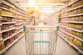 Supermarket aisle with empty red shopping cart Royalty Free Stock Photo