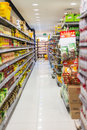Supermarket aisle and shelves displaying variety of groceries product Stock Photos
