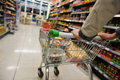 Supermarket aisle view of a shopping trolley and shelves image has a shallow depth of field Royalty Free Stock Photos