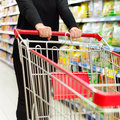 Supermarket cart lady pushing a shopping in the Royalty Free Stock Photos