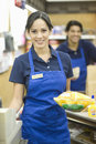 Supermarket employee in blue apron portrait of male and female employees Stock Photos