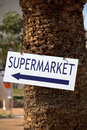 Supermarket sign on tree trunk Stock Photography