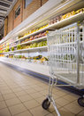Supermarket trolley against the shelves with products fragment Stock Photo