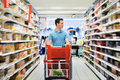Supermarket young man with the cart in the Stock Images