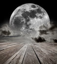 Supermoon sky surreal night with a full moon in the horizon of an empty grungy timber deck platform elements of this image Royalty Free Stock Photo
