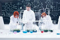 Supervised laboratory experiment general view of one men in a chemistry lab supervising two women manipulating lab tools with Stock Photography