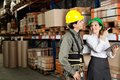 Supervisor with foreman pointing at stock on female shelves in warehouse Stock Photo