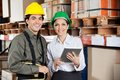 Supervisor instructing foreman at warehouse young female Stock Image
